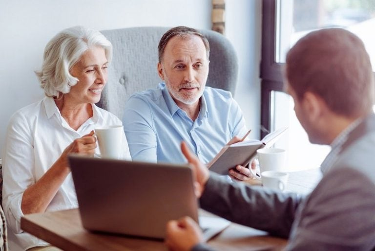 Positive aged couple consulting with insurance agent